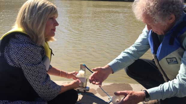 Mike Stainton, Lake Winnipeg Foundation adviser and aquatic chemist, demonstrates the  organization's citizen science water sampling method to Cathy Cox, Manitoba Sustainable Development minister (left), on Tuesday in Winnipeg.