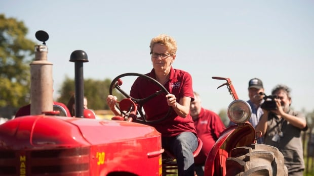 Ontario Premier Kathleen Wynne takes part in a plowing competition during the International Plowing Match in Harriston, Ont. on Tuesday. She was booed several times by the crowd during a speech when she mentioned hydro rates.