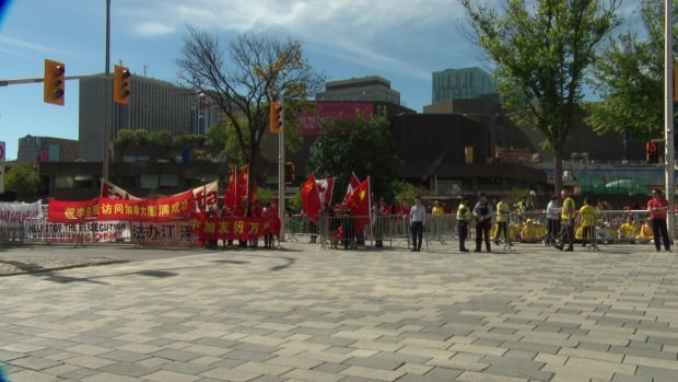 Chinese demonstrators gather across from the Shaw Centre in Ottawa