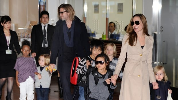 Accompanied by their six children in 2011, Brad Pitt and Angelina Jolie appear before photographers upon their arrival in Tokyo. The family has asked for privacy following Jolie's filing for divorce.
