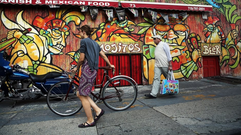 People walk down a popular shopping street in the rapidly developing neighbourhood of Dumbo in the Brooklyn borough of New York City.