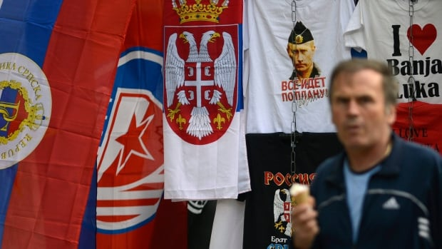 A Bosnian man passes the flag of Republika Srpska and a T-shirt with a photo of Russian President Vladimir Putin in the Bosnian town of Banja Luka on Sept. 21.  Republika Srpska held a referendum on whether to approve a national holiday on Jan. 9. The result was overwhelmingly in favour.
