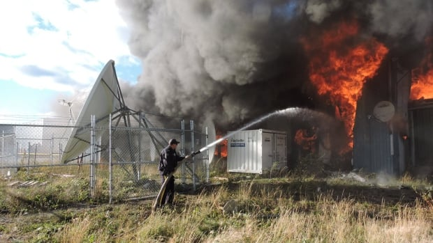 An RCMP officer works to douse flames at the band office and Northern store which burned to the ground in Sept. 2016.