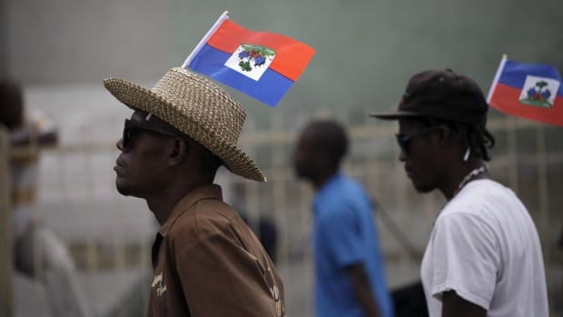 Two protesters carrying Haitian flags on their heads march during a demonstration against the electoral process in Port-au-Prince, Haiti. Canada has told Haiti it will not provide additional funds to rerun its election next month; international observers say the result should have stood when Haitians went to the polls last year.