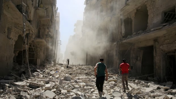 Men inspect the damage after an airstrike on a rebel-held neighbourhood in Aleppo on Sunday.