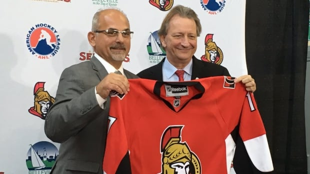 Belleville Mayor Taso Christopher (left) holds up a sweater with Ottawa Senators owner Eugene Melnyk, who bought the Binghamton Senators and signed an eight-year deal to move them to Belleville.