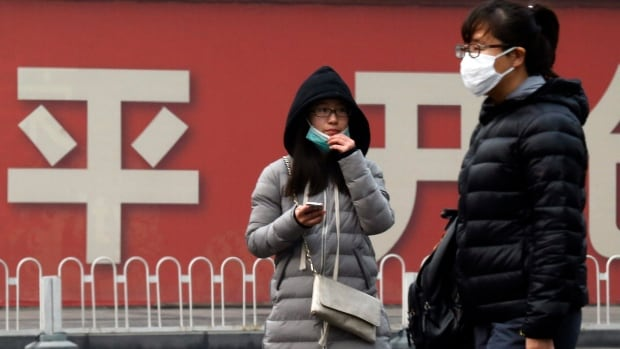 Residents wear masks for protection from smog during a day of heavy pollution in Beijing, China, in December 2015. Coal-fired power plants, household burning of