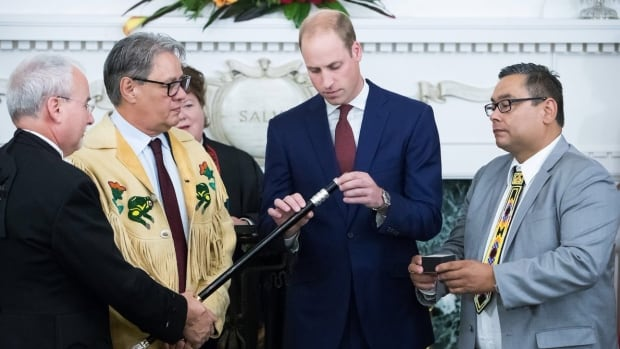 First Nations Summit Grand Chief Ed John, left, and B.C. Regional Chief Shane Gottfriedson, right, look on as Prince William adds a fourth ring representing reconciliation to the provincial legislature's Black Rod.