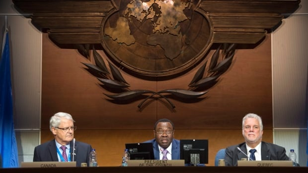 ICAO president Olumuyiwa Benard Aliu addresses the opening session of the 39th assembly of UN aviation agency in between Transport Minister Marc Garneau, left, and Quebec Premier Philippe Couillard on Tuesday in Montreal.