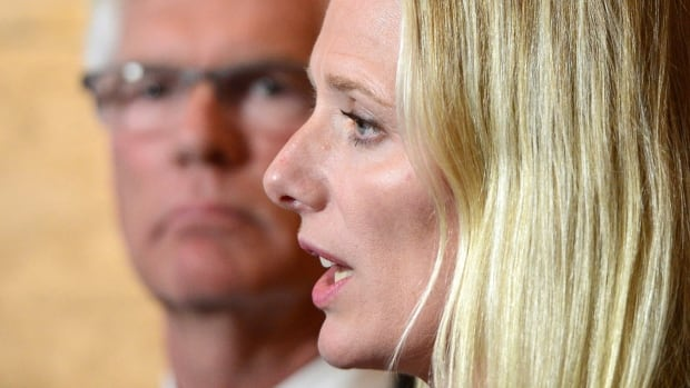 Environment Minister Catherine McKenna speaks to reporters following a caucus meeting on Parliament Hill in Ottawa Wednesday, as Natural Resources Minister Jim Carr, left, looks on.