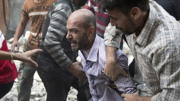 A grief-stricken Syrian man looks on as rescuers pull the body of his daughter from the rubble of a building following government airstrikes in Aleppo on Sept. 27.