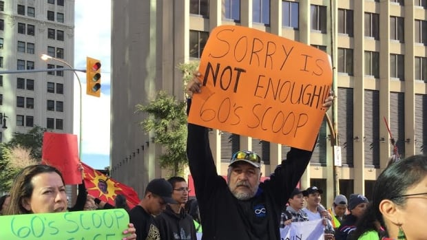 Sixties Scoop marchers carry signs calling for compensation and support from the government.