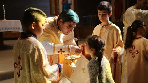 Father Ephrem Kardouh serves communion to a young girl at St. Basil's Melkite Greek Catholic Church. A majority of his congregation are immigrants from the Middle East.