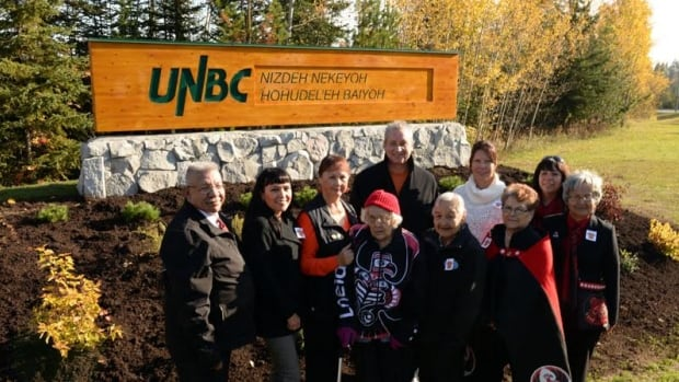 Lheidli T'enneh leaders and elders pose outside the new university sign utilizing the Dakelh language.