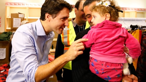 Syrian refugees are greeted Prime Minister Justin Trudeau on their arrival from Beirut at the Toronto Pearson International Airport in Mississauga, Ontario, in December, 2015.  About 77 per cent of those asked indicated they were now happy or very happy with their lives in Canada.