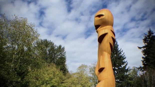 The 10-foot-tall yellow cedar sculpture is largely abstract, but it features the head of a being at the top.