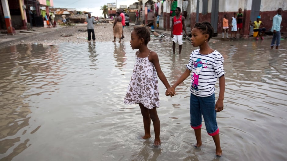 town like a wasteland after hurricane matthew home as  girls hold hands as they help each other wade through a flooded street after the passing