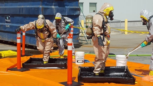 In this June 27, 2016 photo provided by the Royal Canadian Mounted Police, members of the RCMP go through a decontamination procedure in Vancouver after intercepting a package containing approximately one kilogram of the powerful opioid carfentanil imported from China.