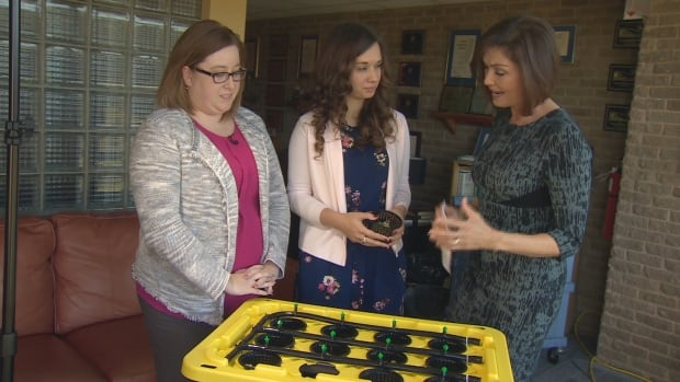 Abbie Ricketts (left) and Emily Bland (middle) from Memorial University, explaining to CBC host Debbie Cooper how the hydroponics unit works.