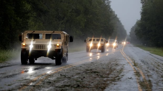 Military vehicles travel a highway near Wagram, North Carolina on Saturday, joining storm recovery efforts.