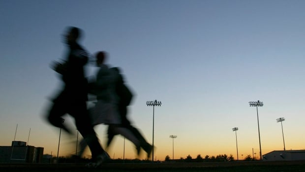 In this Thursday, Jan. 22, 2004 file photo, students jog around a stadium at sunset in Bowling Green, Ky. A large, international study released on Monday, Oct. 10, 2016, ties heavy exertion while stressed or mad to a tripled risk of having a heart attack within an hour.