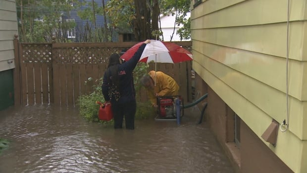 Sydney residents work to pump floodwater from their home Thanksgiving Day after 225 millimetres of rain fell in 24 hours.