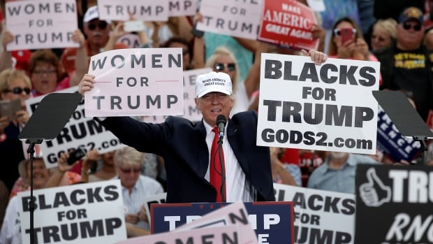 Republican U.S. presidential nominee Donald Trump holds up signs at the end of a campaign rally in Lakeland, Fla., on Wednesday.