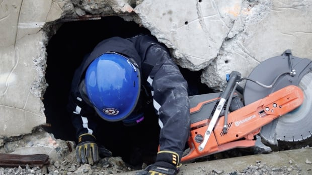 Can TF1 member and paramedic Sean Penner crawls out of a pile of rubble used to stage earthquake rescue exercises.