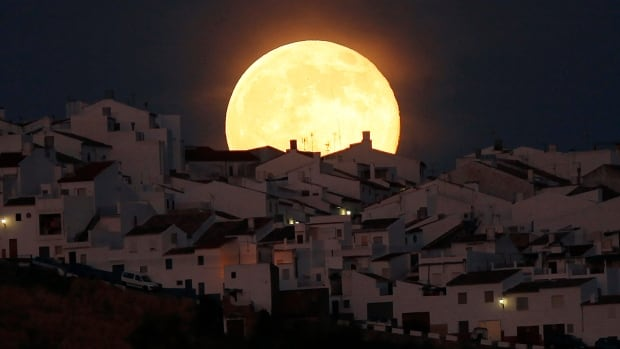 A supermoon rises over houses in Olvera, in the southern Spanish province of Cadiz, in July 2014.