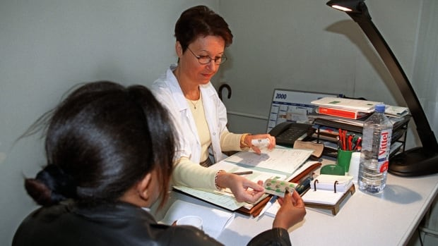 A doctor gives a woman RU486 pills at clinic in France, where it's been available since 1988.