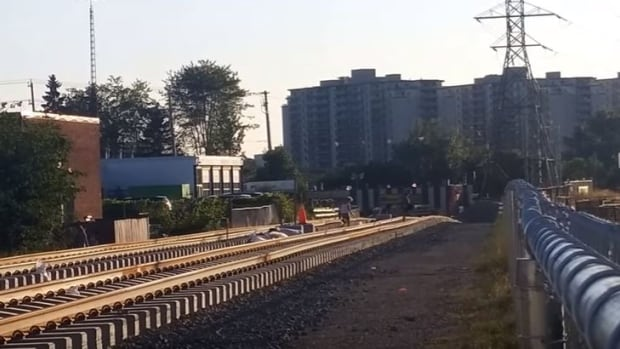 Residents cross over LRT tracks near Traynor Avenue in Kitchener in a still from a YouTube video.