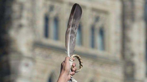 An eagle feather, an Indigenous symbol, is held up on Parliament Hill. The Algonquins of Ontario are one step closer to assuming tens of thousands of acres of their ancestral territory in a historic treaty.