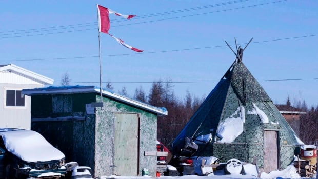 The remains of a Canadian flag can be seen flying over a building near the school in Attawapiskat, Ont.