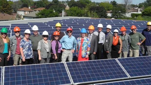 Members of the Ottawa Renewable Energy Co-Operative celebrate the installation of a feed-in tariff solar project on the roof of an Ottawa high school. The co-op leases the roof space from the school, which uses the funds for green education programs for its students.