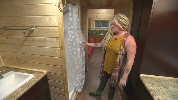 Anita Munn inspects the handywork in one of the tiny bathrooms built by her and her partner, Darrell Manuliak.