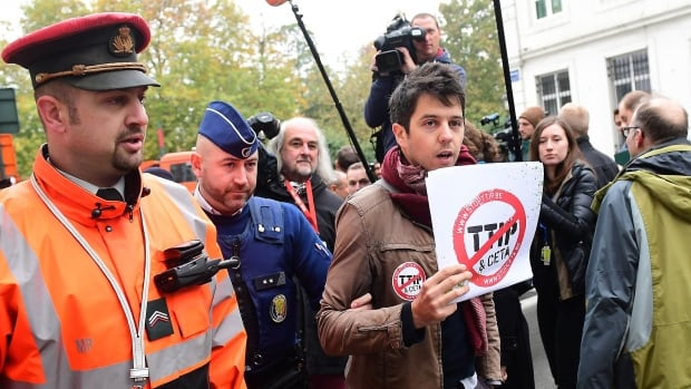 A demonstrator is led away by a policeman as he holds a poster reading 'Stop TTIP - Stop CETA' ahead of an emergency meeting of all Belgium federal entities on the EU-Canada Comprehensive Economic and Trade Agreement (CETA) in Brussels on Monday.