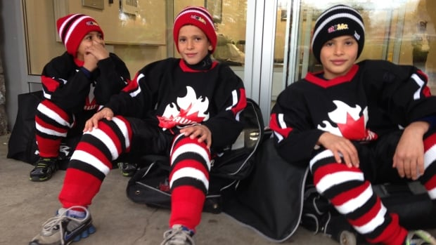 Ismael Yasen, 9, Ahmad Al-Masri, 8 and Mohammed Al-Masri, 9, wait outside their Ottawa apartment building for Allan Martel to pick them up and take them to the rink.