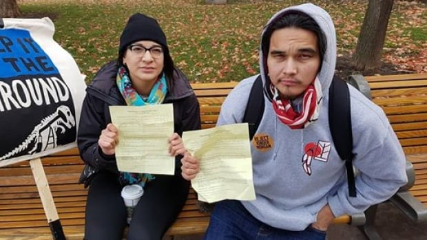 Sadie-Phoenix Lavoie and Kevin Settee hold up their court papers after they were ticketed for trespassing at Parliament Hill in Ottawa on Monday.