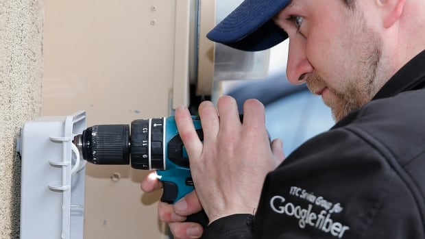 Jeffrey Ohngren, a Google Fiber technician installs a fibre-optic box at a residential home in Provo, Utah, Jan. 2, 2014. The company has halted further expansion of its high-speed network.
