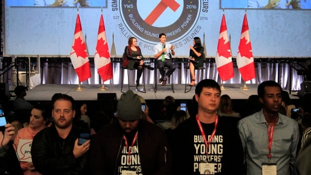 Youth protesters turn their backs on Prime Minister Justin Trudeau as he addresses the Canadian Labour Congress National Young Workers' Summit in Ottawa on Tuesday.