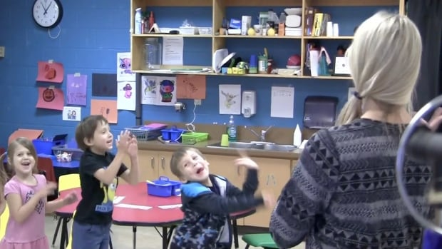 Students at John J. Sark Memorial school dance to the music with their part-time music teacher.