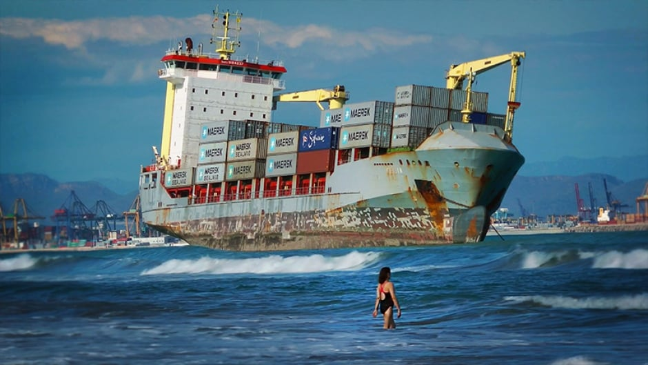 Swimmers share the beach with a rusty container ship