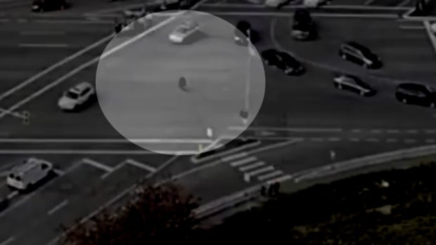 Drone footage appears to show a pedestrian cutting diagonally across several lanes of moving traffic in the intersection at Highway 17 and 52 Street, ignoring marked crossings. Highlight alteration performed by CBC.