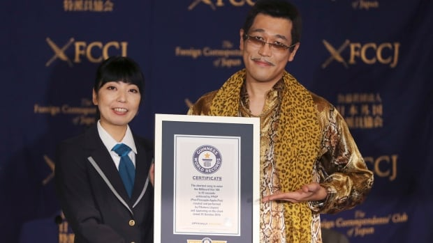 Japanese comedian Pikotaro, right, receives a Guinness World Records certificate for his viral hit PPAP (pen-pineapple-apple-pen), the shortest song to enter the U.S. Billboard Hot 100 Chart.