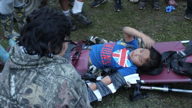 Jedediah Barkman is comforted while waiting for a medical driver to pick him up from the Sachigo Lake First Nation baseball field where he broke his arm.