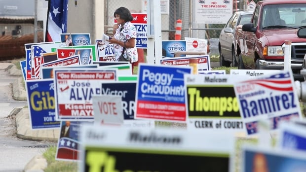 Signs for local candidates clutter an area outside an Osceola County polling station in Kissimee, Fla., on Oct. 25, 2016.