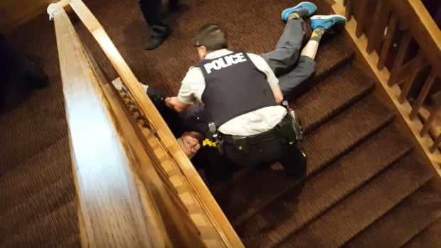 An unruly condo board meeting led to police dragging away an elderly couple who allegedly refused to leave.