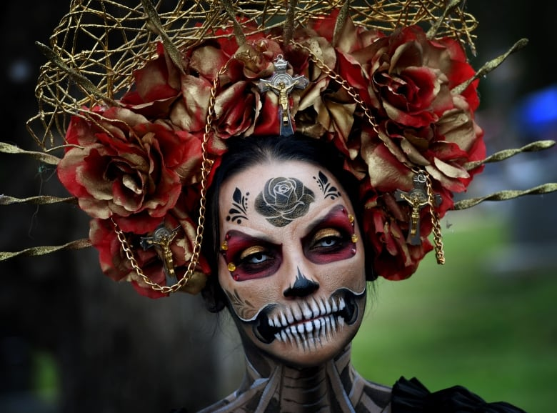 a woman dressed in a skeleton costume parades during the annual dia de los muertos day of the dead festival at the hollywood forever cemetery in
