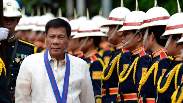 Philippine President Rodrigo Duterte walks past honour guards of the Philippine National Police in Manila on July 2016.  Two officers, who spoke on condition of anonymity, recently told Reuters PNP forces get cash bonuses for killing drug suspects.