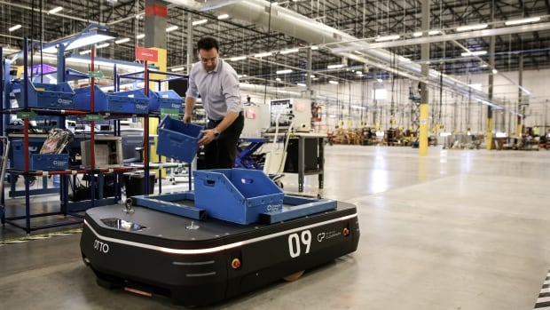 Adam Gryfe, director of strategic initiatives at Kitchener, Ont.-based Canadian tech startup Clearpath Robotics, works with the company's self-driving robot for the factory floor.